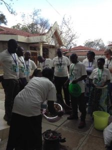 Photo showing Wilimina teaching on making medicinal charcoal from groundnut shells