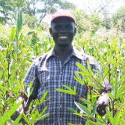 Samuel Ouma in a field of Roselle
